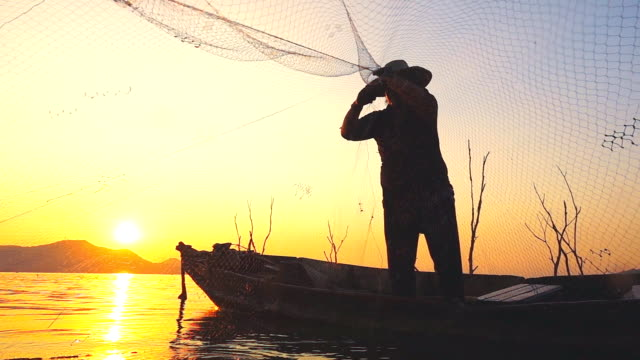 hd slow motion: fisherman on boat fishing at sunset - agricultural equipment stock videos & royalty-free footage