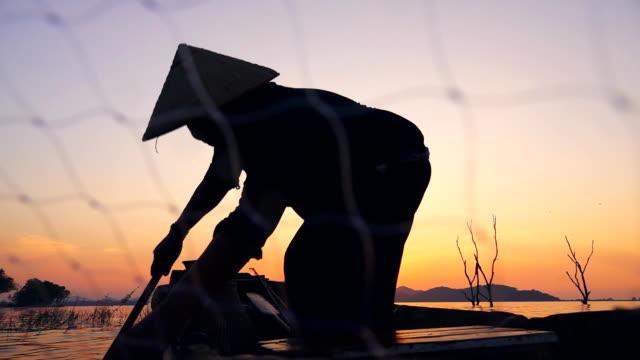 stockvideo's en b-roll-footage met hd slow motion: visser over de longtail boot visserij bij zonsondergang in thailand - hengel uitwerpen