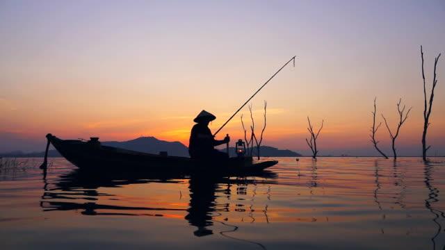 vidéos et rushes de hd slow motion: pêcheur sur la pêche en bateau longtail au coucher du soleil en thaïlande - lancer la ligne de canne à pêche