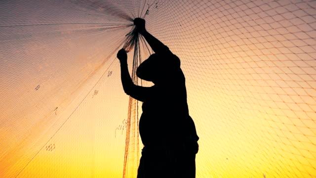 vidéos et rushes de hd slow motion: pêcheur sur longtail bateau de pêche au coucher du soleil - lancer la ligne de canne à pêche