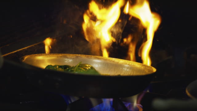 slow motion flambe spinach and mushrooms over commercial range - mexican food stock videos & royalty-free footage