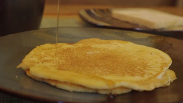slow motion: flat pancake stack being drizzled with syrup - stack of plates stock videos & royalty-free footage