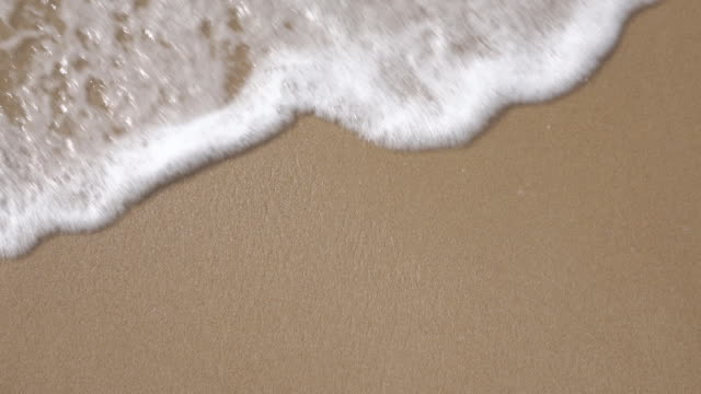 slow motion foam wave on the beach - sand stock videos & royalty-free footage