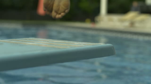 vídeos de stock e filmes b-roll de slow motion focus on diving board and feet launching into water, spain (individual frames may also be used as a still image. each frame in its raw state is about 6mb or about 12mb as a 16 bit tiff) - câmara lenta