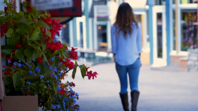 slow motion focus transition: flowers and young woman walking away then turning - window box stock videos & royalty-free footage