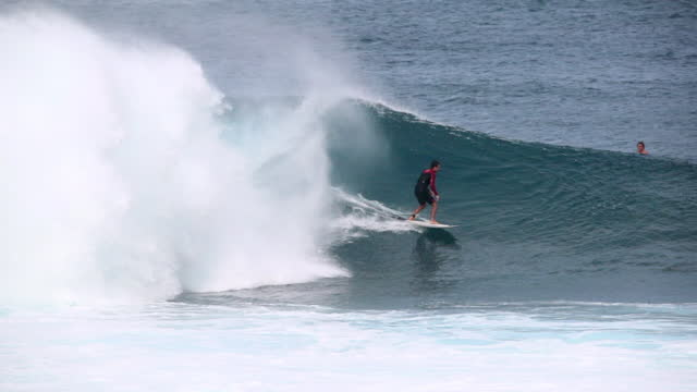 slow motion following a surfer riding an immense barrel wave with deep blue ocean and white surf - oahu, hawaii - overcast stock-videos und b-roll-filmmaterial