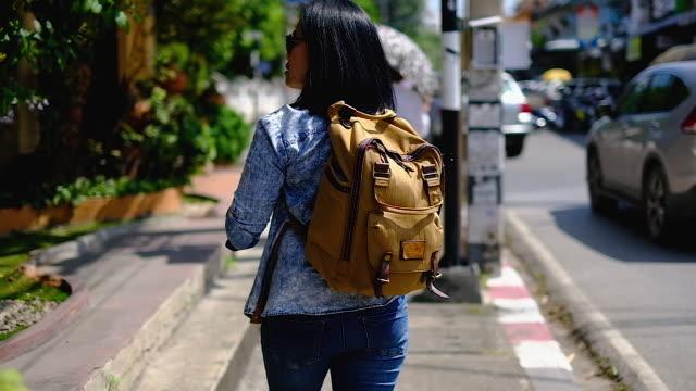 vidéos et rushes de ralenti à la suite d'asiatique femme marchant en city.urban mode de vie - sac à dos
