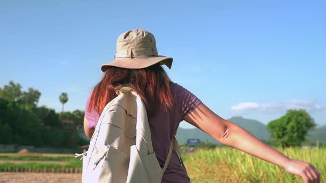 vidéos et rushes de ralenti suivant la vue arrière: femme asiatique marchant avec drôle sur la crête du rizière entre l'oreille de riz et le riz récolté sous le coucher du soleil dans une scène agricole non urbaine, le nord de la thaïlande avec un sentiment excité, - non urban scene