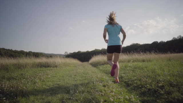 slow motion following woman jogging through high grass in summer