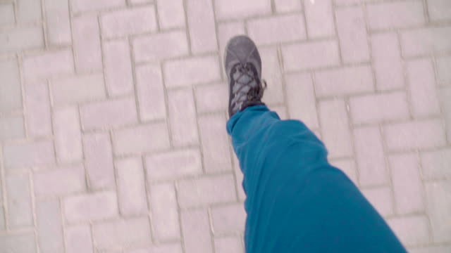 Slow motion: POV foot running on the pavement