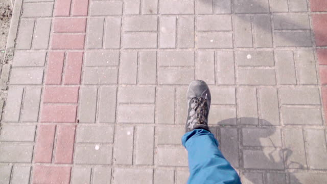 Slow motion: POV foot walking on the footpath