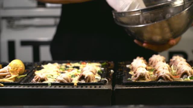 vídeos de stock, filmes e b-roll de 4k câmera lenta mão closeup de filmagens de chef de cozinha e acrescentando ingredientes polvo de comida japonesa de takoyaki na pan, o estilo tradicional e o conceito de comida de rua - comida japonesa