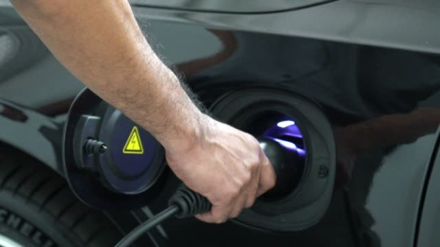 4k slow motion footage closeup hand of man plugging in hybrid electric vehicles for charging battery car, transportation and car service concept - fare il pieno di benzina video stock e b–roll