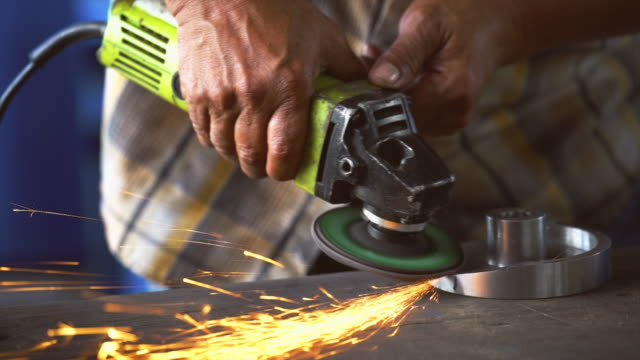 4k slow-motion aufnahmen closeup winkelschleifer hand hält und schleifen die ersatzteile aus metall über den holztisch in metallfabrik, industrie und maschine konzept - 4k auflösung stock-videos und b-roll-filmmaterial