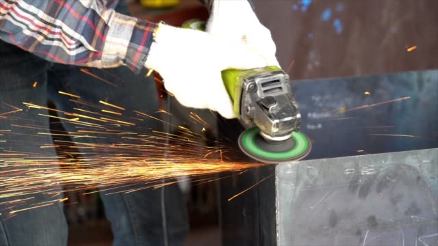 vídeos de stock, filmes e b-roll de imagens de câmera lenta 4k closeup de mãos usando a rebarbadora de corte e moagem de peças de aço do metal na fábrica de metal, indústria e máquina conceito - arco característica arquitetônica