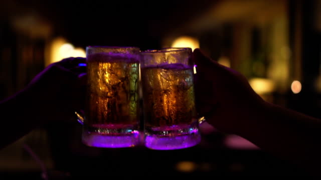 4 k スローモーション映像で一緒に応援して、ビールの乾杯と素晴らしく眼鏡のクローズ アップ バーとレストラン、リラックス、概念を飲む - bar点の映像素材/bロール
