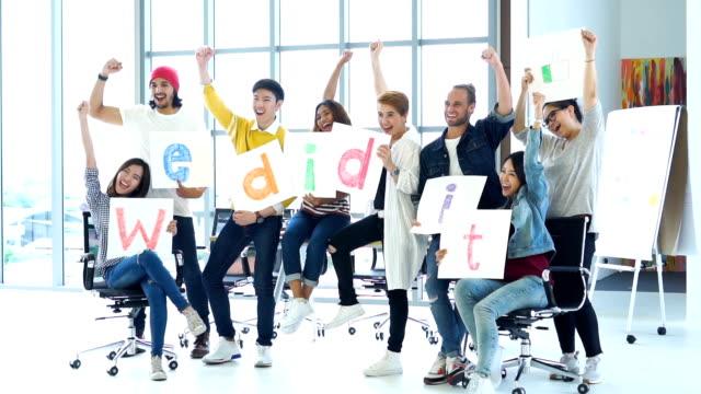 fhd slow-motion aufnahmen gruppe der asiatischen und diverse geschäftsleute mit lässigen anzug freut sich, die arme nach oben und gratulation mit wörtliche übersetzungstext in der modernen arbeitswelt, teamwork konzept erhöhen - gratulieren stock-videos und b-roll-filmmaterial