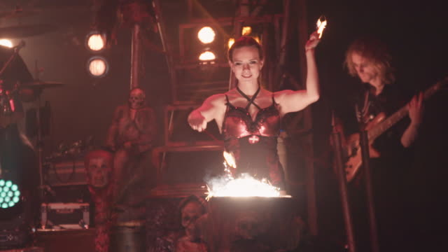slow motion footage of a female circus performer drumming with sticks of fire - musical burlesco video stock e b–roll