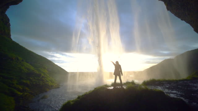 vídeos de stock, filmes e b-roll de slow motion footage of a girl standing in front of seljalandsfoss waterfall in golden time, iceland - cachoeira de seljalandsfoss