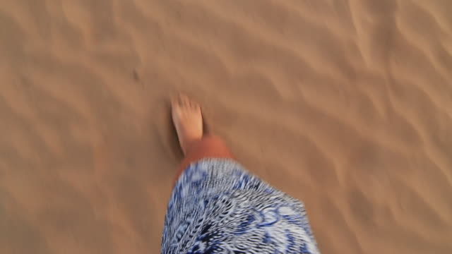 Slow motion footage of a guy running barefoot from personal perspective in the sand dunes of the Essaouira beach during travel vacations in Morocco.