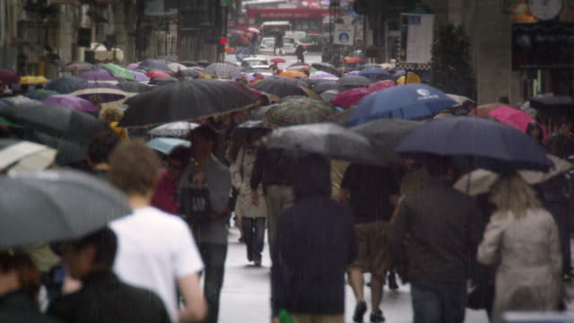 Slow motion footage of a street filled with people holding umbrellas