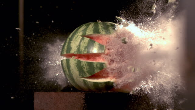 Slow motion footage of a watermelon being hit by a bullet and exploding