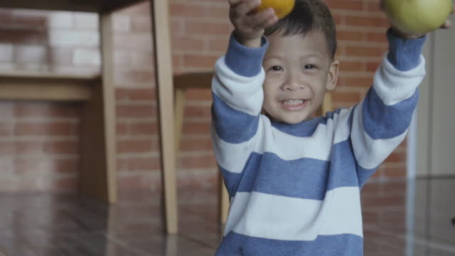 4k slow motion footage of asian little boy holding orange and apple with smiling full of happiness life at modern loft house, family and childhood concept - apple fruit stock videos & royalty-free footage
