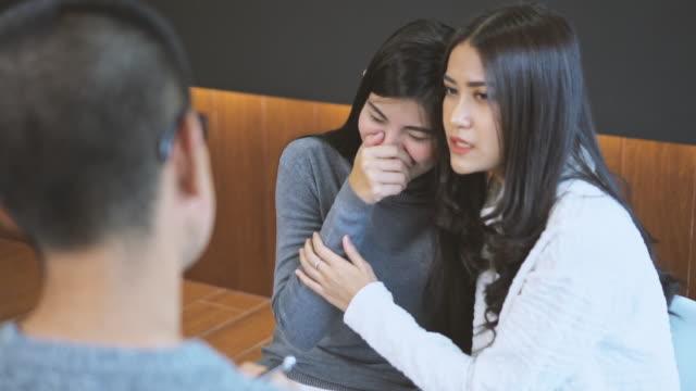 とめた精神保健精神療法コンセプト家や病院の診察室のモダンなリビング ルームに関係する問題についての恋人カップル レズビアン患者に慰めを与えるアジア人専門の心理学者博士のスロ� - 催眠状態点の映像素材/bロール