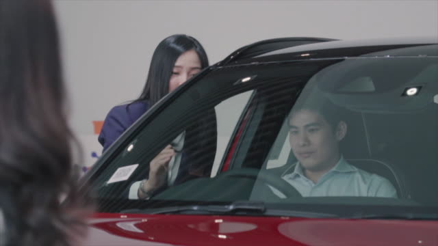 4k slow motion footage of asian saleswoman introducing customer to test drive in showroom - car showroom stock videos & royalty-free footage