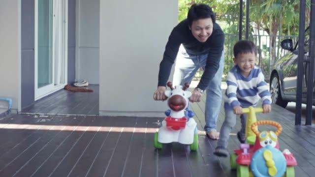 4K slow motion beelden van Aziatische single papa met zoon spelen speelgoed auto samen in front gazon van modern huis voor zelf leren of thuisschool, familie en jeugd concept