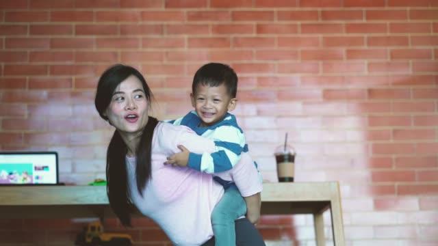 息子と一緒にアジアのシングルママの4k スローモーション映像は、自己学習や家庭の学校、家族や子供の頃のコンセプトのための近代的なロフトハウスで幸せの生活の完全に一緒に遊んでい� - 子守り点の映像素材/bロール