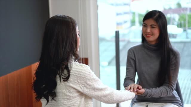 とめた精神保健精神療法コンセプト家や病院の診察室のモダンなリビング ルームで女性患者に慰めを与えるアジア女性専門の心理学者医師のスローモーション映像を 4 k - 催眠状態点の映像素材/bロール