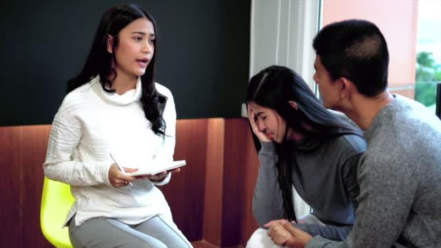 vidéos et rushes de images de slow motion 4k de médecin psychologue professionnel de femme asiatique donnant réconfort au patient couple amant sur problème de relation dans la moderne salle de séjour de la maison ou hôpital salle d'examen, la santé mentale de l'hypn - hypnose