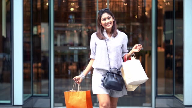 4k slow motion footage of asian woman walking out from the department store and holding the shopping bags in downtown, fashion and shopping center concept - lentezza video stock e b–roll