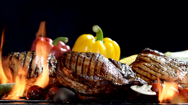 Slow motion footage of assorted grilled meat with vegetable on the flaming grill