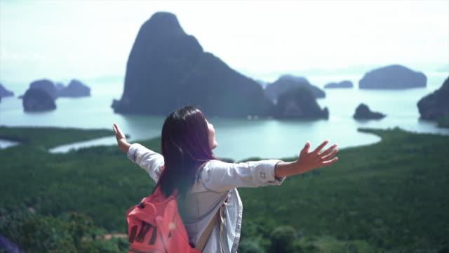 vídeos y material grabado en eventos de stock de 4k lenta de atractivo asiático viajero mujer levante el brazo por encima de la montaña mirando a ver, sentir libertad y disfrutar de la naturaleza en el concepto de estilo de vida de samed nang chee, viajes y felicidad - brazo humano