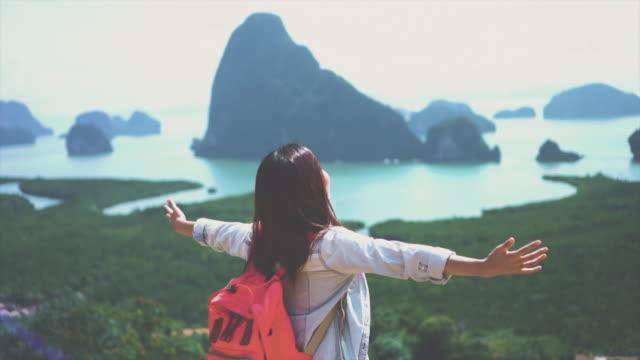 4k slow-motion aufnahmen von attraktiven asiatischen frau reisenden arm heben auf berg betrachten, freiheit spüren und genießen sie die natur bei samed nang chee, reisen und glück-lifestyle-konzept - rucksack stock-videos und b-roll-filmmaterial