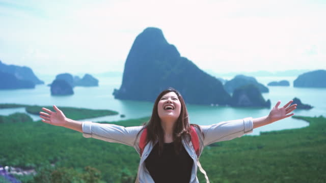 4k slow motion footage of attractive asian woman traveler raise arm up on top of mountain looking at view, feel freedom and enjoy nature at samed nang chee, travel and happiness lifestyle concept - tourist stock videos & royalty-free footage