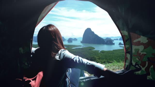4k slow-motion aufnahmen von attraktiven asiatin reisenden im zelt sitzen und betrachten des berges, freiheit spüren und genießen sie die natur bei samed nang chee, reisen und glück-lifestyle-konzept - zelt stock-videos und b-roll-filmmaterial
