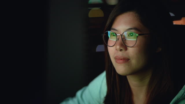 4K Slow motion footage of Attractive Asian woman wearing glasses working late and looking screen with serious action on the table in front of computer monitor desktop at workplace in the dark, Work late and Work hard concept