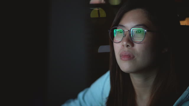 4k slow motion footage of attractive asian woman wearing glasses working late and looking screen with serious action on the table in front of computer monitor desktop at workplace in the dark, work late and work hard concept - asian and indian ethnicities stock videos & royalty-free footage
