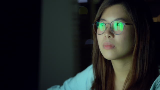 vídeos de stock e filmes b-roll de 4k slow motion footage of attractive asian woman wearing glasses working late and looking screen with serious action, work late and work hard concept - east asian ethnicity
