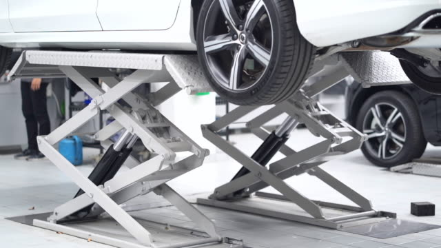 4k slow motion footage of car lifted in automobile service, transportation and maintenance car concept - lug wrench stock videos and b-roll footage