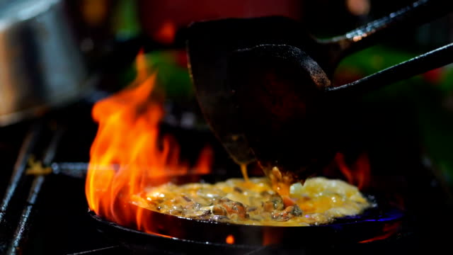 FHD Slow motion footage of closeup cooking Fried Shrimp stir-fried by spade of frying pan over pan, Thailand tradition food, asian food