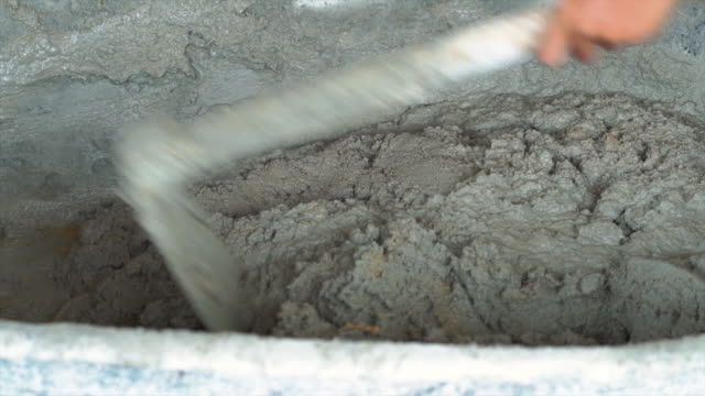 4k slow motion footage of closeup mixer operator mixing mortar and sand in concrete mixer tray at new construction site, construct industry and masonry concept - wheelbarrow stock videos and b-roll footage