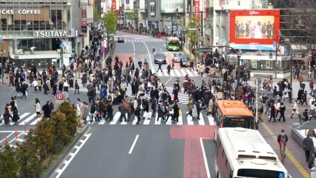 4K Slow Motion-Footage von Menschenmassen Fußgänger zu Fuß über die Straße Kreuzung Kreuzweg und Verkehrswagen in Shibuya Bezirk Tokyo Stadt, Japan. Japanisches Kultur-und Einkaufsbereichskonzept