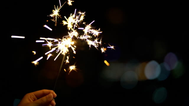 4k slow motion footage of handheld sparklers firework sparkling at night time with blurred of light bokeh city background, celebrating with happy new year and party concept - firework display stock videos & royalty-free footage