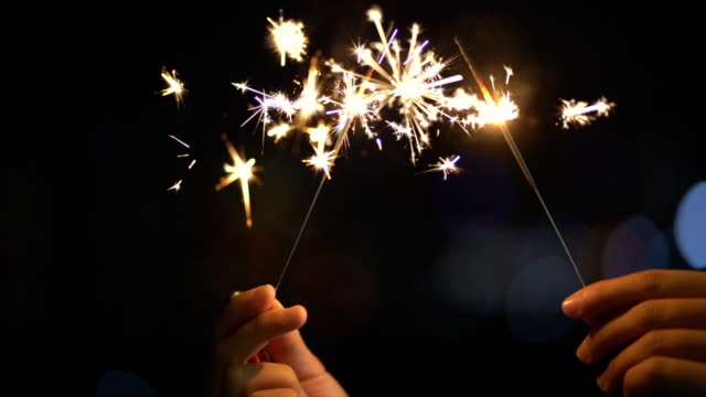 4k slow motion footage of handheld sparklers firework sparkling at night time with blurred of light bokeh city background, celebrating with happy new year and party concept - anniversary stock videos & royalty-free footage
