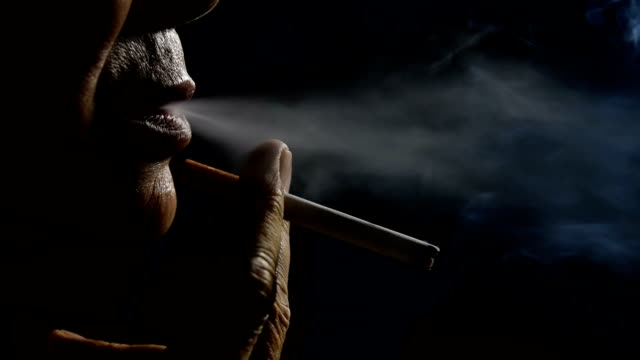 slow motion footage of man smoking on black background - smoke physical structure stock videos and b-roll footage