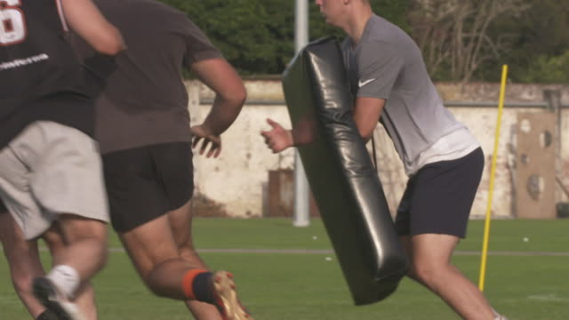 Slow motion footage of rugby players in huddle taking break passing ball and tackling team mates using pads during training